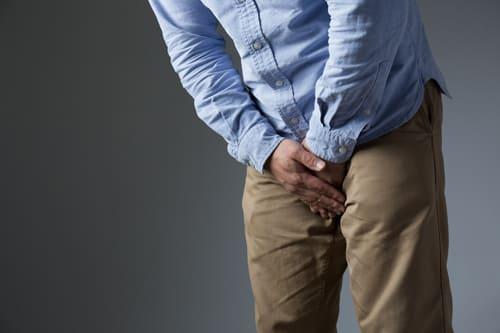 股間を押さえる男性の画像
