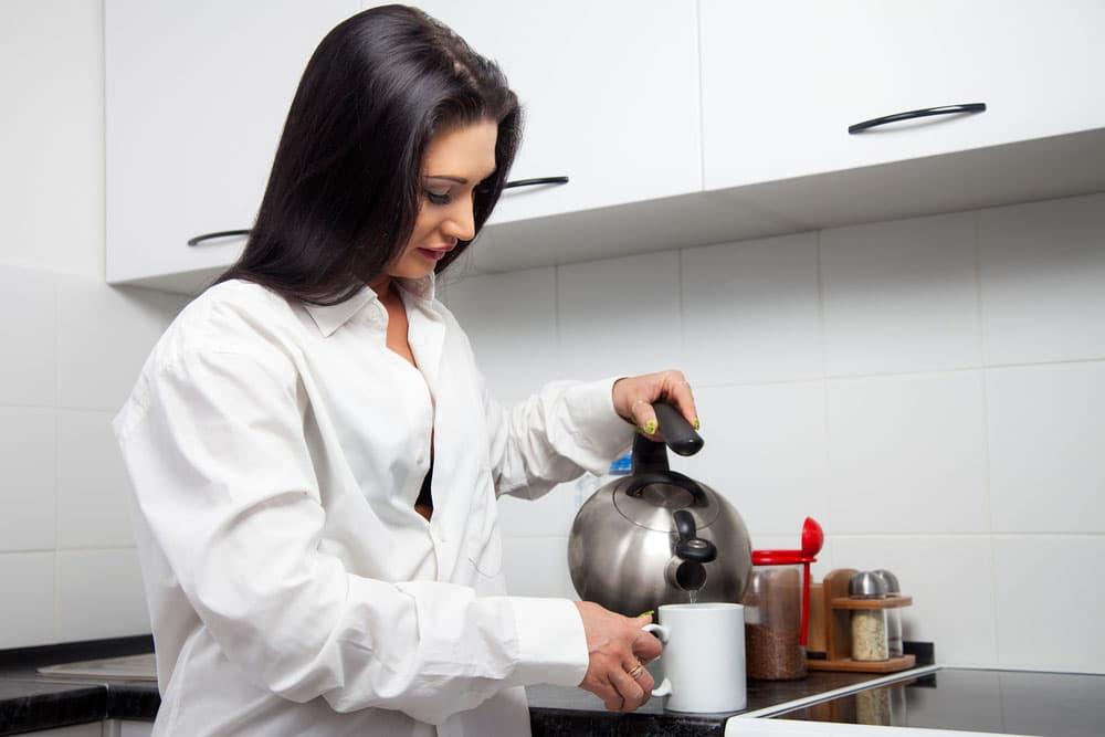 ガスを使ってお湯を沸かしている女性
